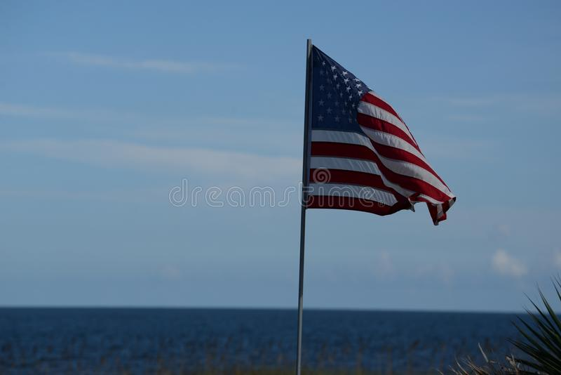 Vinden kommer med en våg till amerikanska flaggan som flyger över en beachfront tystnad royaltyfria foton