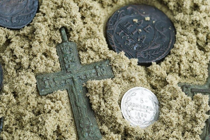 Vindend schatjager op het zand, de oude kruisen tussen hen een zilveren muntstuk 5 centen 1892 royalty-vrije stock afbeelding