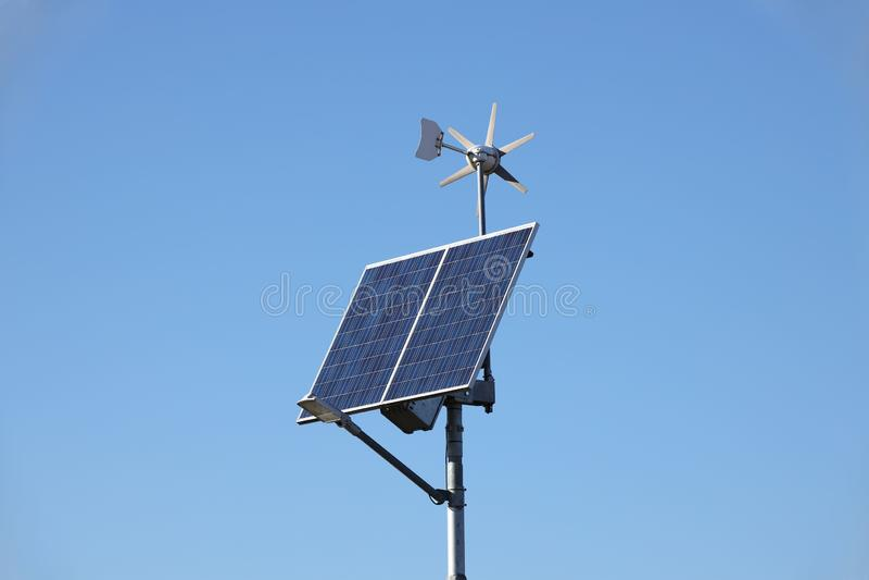 Vindgenerator och solpanel på en blå himmel photovoltaic celler Metod av att erhålla alternativ energi Ekologiskt rengöring royaltyfri fotografi