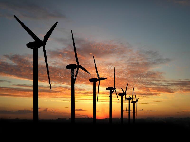 Vindgeneratorer på den härliga solnedgången arkivbild