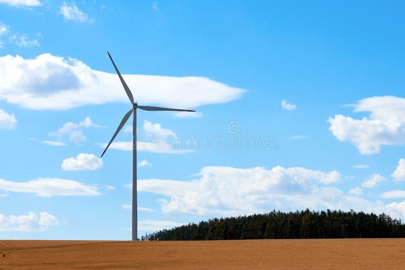 Vindkraftstation med en pol och väderkvarn, nära skog och cornfield i bygd under blå himmel med moln royaltyfria foton
