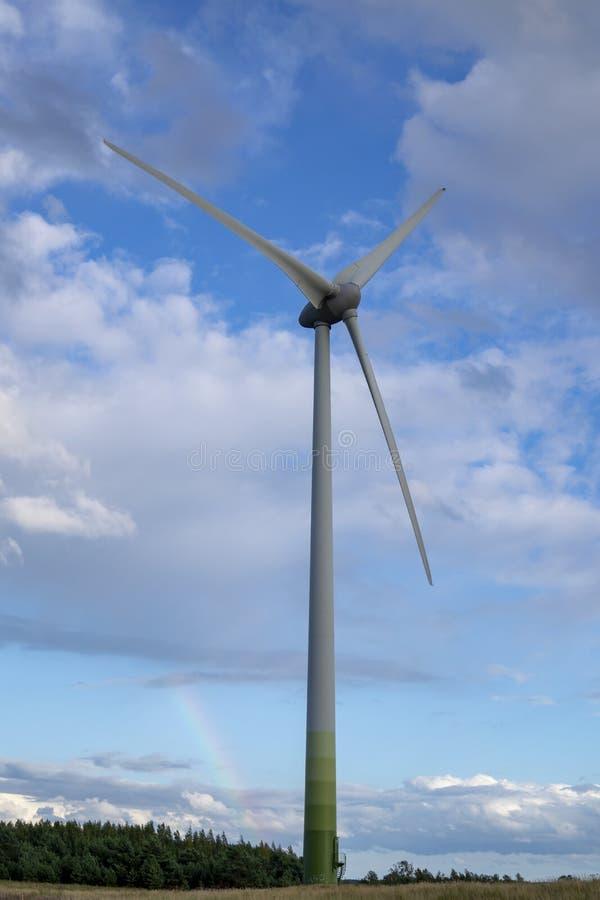 Vindkraftturbin mot molnig blå himmel arkivfoton