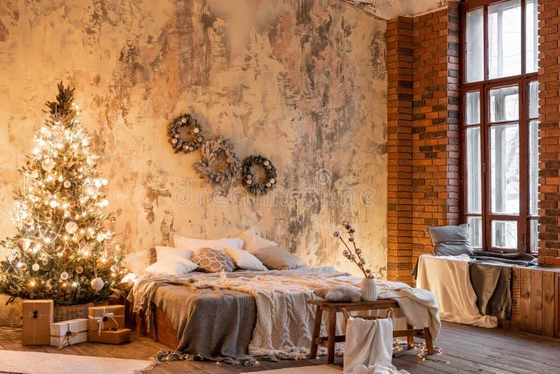 Vindlägenheter, tegelstenvägg med stearinljus och julgrankransen Säng i sovrummet, höga stora Windows royaltyfria bilder