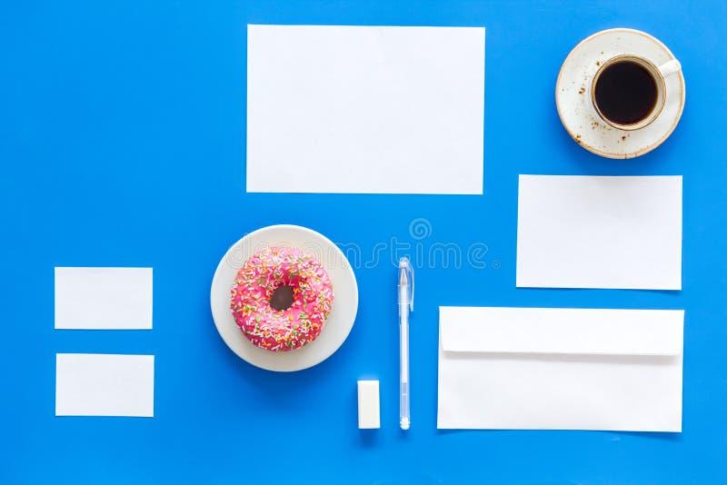 Vindo acima com identidade de marca Artigos de papelaria vazios para marcar perto do café e da filhós no modelo azul da opinião s fotografia de stock