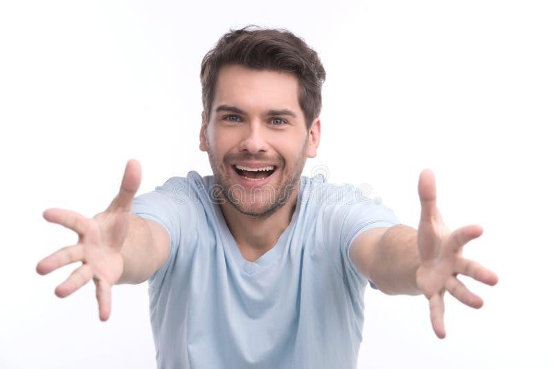 Vindo a mim! Retrato dos homens novos felizes que gesticulam no whil da câmera imagens de stock royalty free