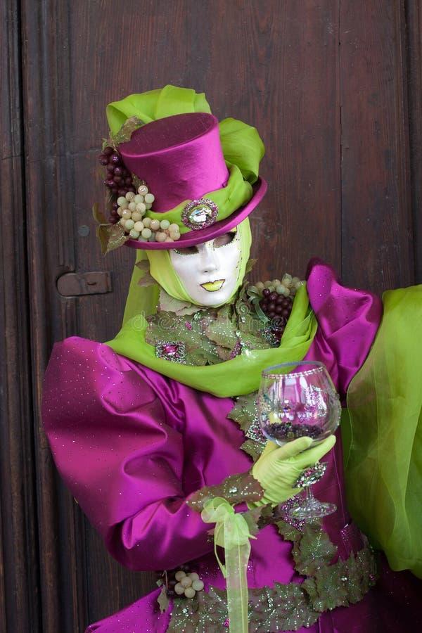 Vindruvorna maskerar att posera med en glass boll i hand arkivfoto