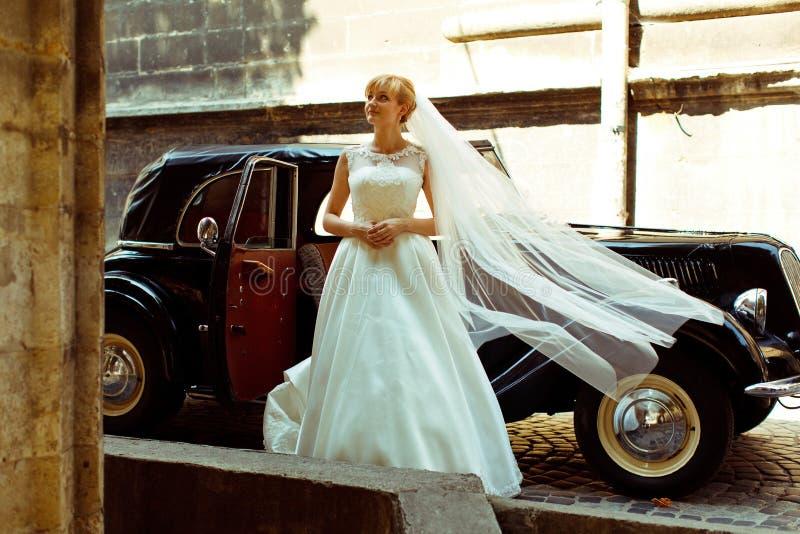 Vindslagbruden skyler bort, medan hon kliver ou av en retro bil arkivfoton
