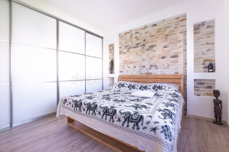 Vindstil planlade sovrummet med dubbelsäng, byggande i garderob, royaltyfri foto