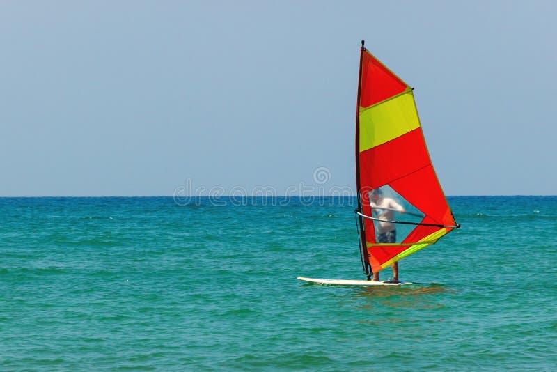 Vindsurfa på bakgrunden av havslandskapet och den klara himlen Surfaremannen går in för sportar, kopieringsutrymme arkivfoto