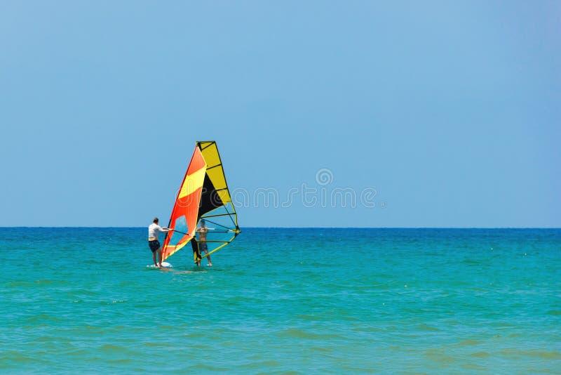 Vindsurfa på bakgrunden av havslandskapet och den klara himlen Två surfaremän går in för sportar, kopieringsutrymme royaltyfria foton