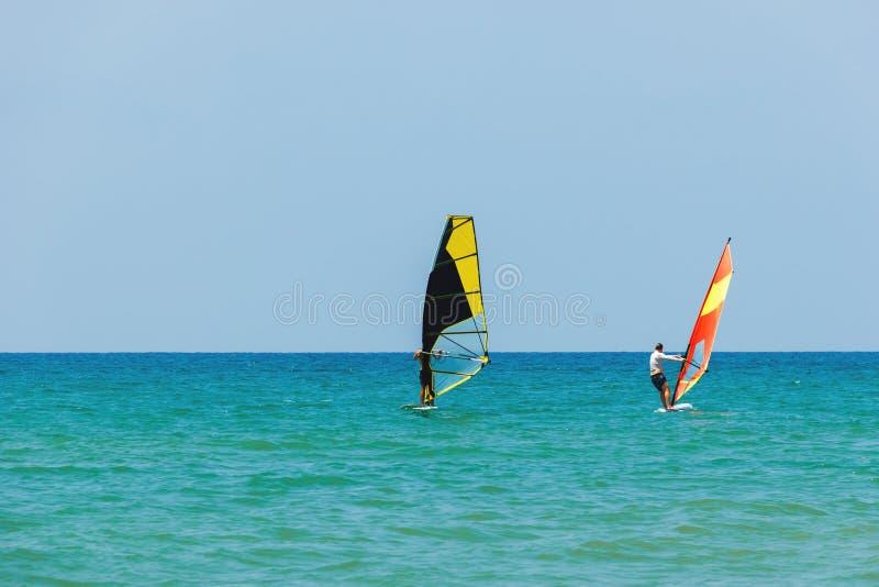 Vindsurfa på bakgrunden av havslandskapet och den klara himlen Två surfaremän går in för sportar, kopieringsutrymme royaltyfri fotografi
