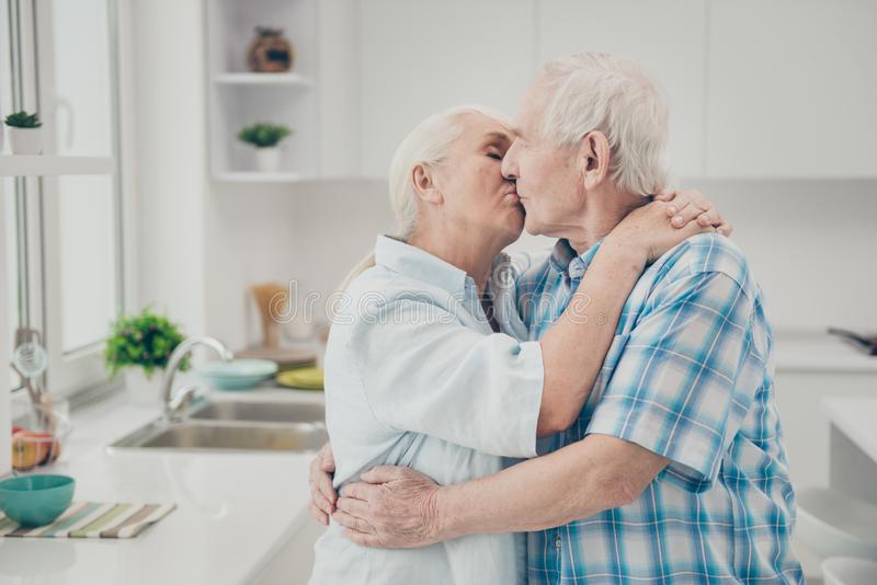 Vindt de profiel zijfoto van het gehuwde liefjes kussen tevreden van bevindende ruimtekeuken binnen geniet royalty-vrije stock afbeelding