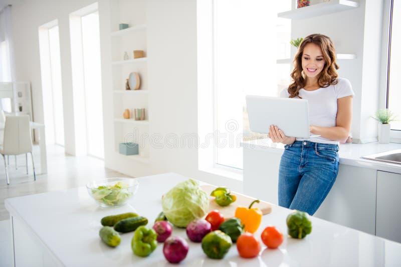 Vindt het aantrekkelijke mooie aantrekkelijke vrolijke vrolijke wavy-haired meisje die van Nice toevallig gebruikend laptop onder stock foto