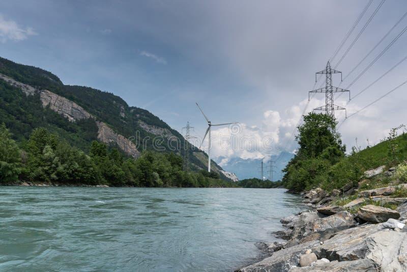 Vindturbin och kraftledningar på bankerna av en flod i en bergdal arkivbilder