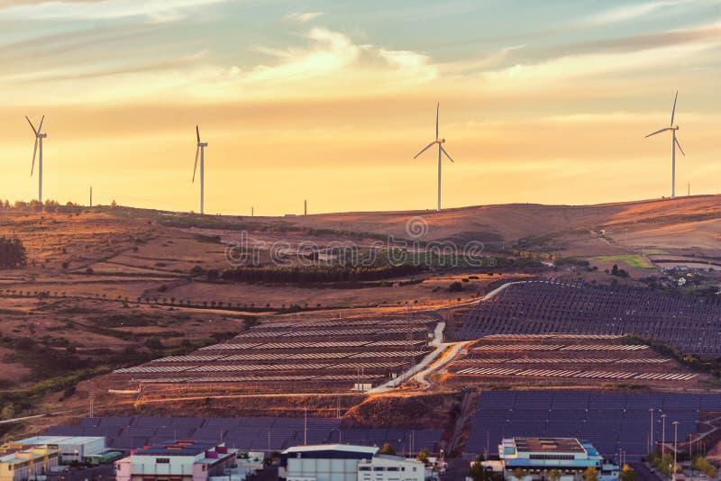 Vindturbinen och solpaneler parkerar på solnedgången arkivfoto