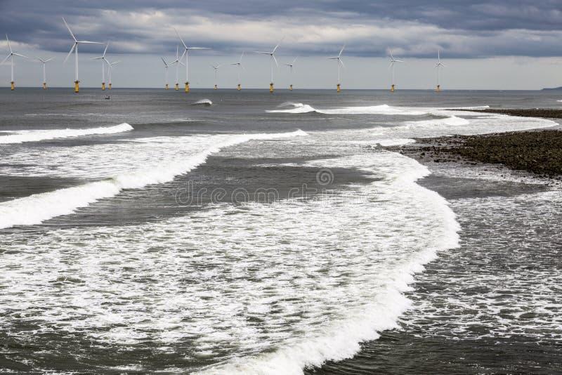 Vindturbiner från kust nära flodutslagsplatsbreda flodmynningen fotografering för bildbyråer