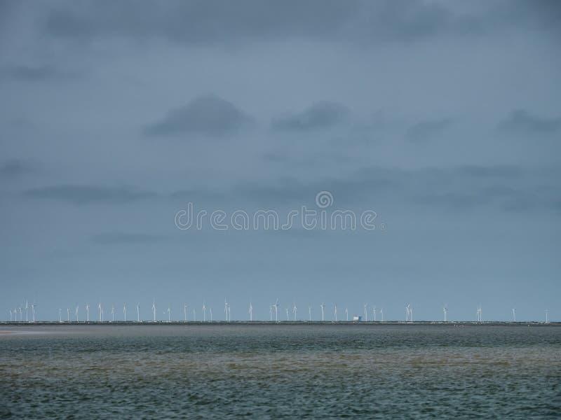 Vindturbiner i Nordsjö som ses från den Blaavand stranden, Danmark royaltyfri foto