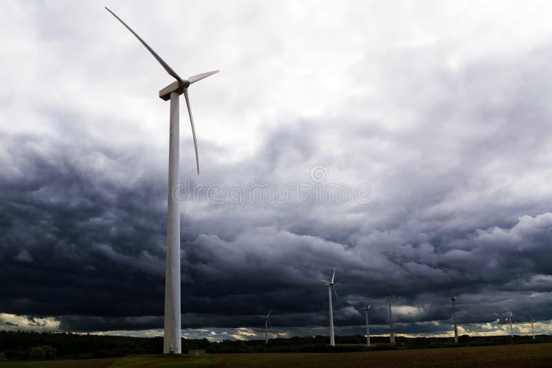 Vindturbiner mot mörker fördunklar i den kommande stormen, begrepp arkivbilder