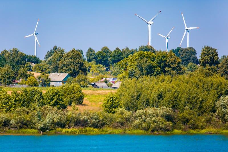 Vindturbiner nära liten by F?rnybara energik?llork?llbegrepp royaltyfria bilder
