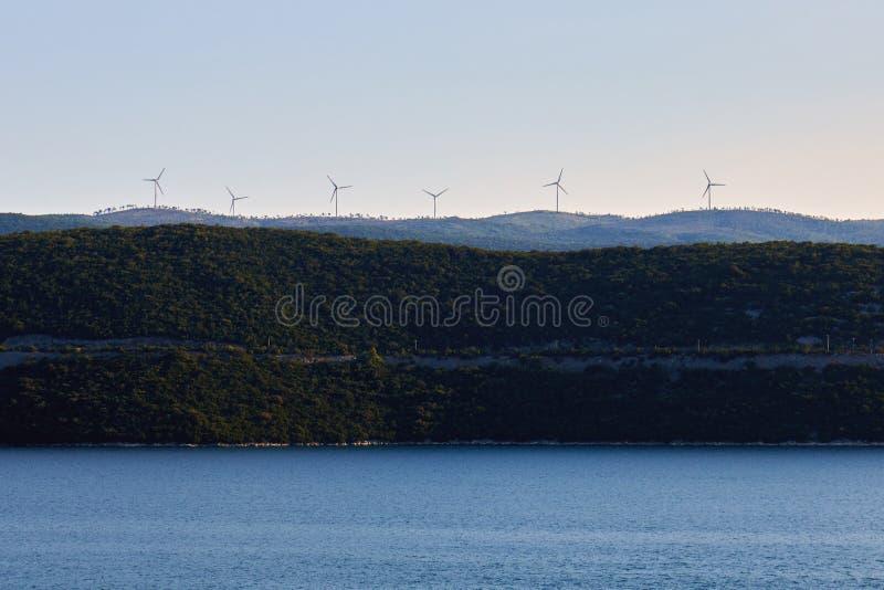 Vindturbiner på kullen ovanför havet royaltyfria bilder