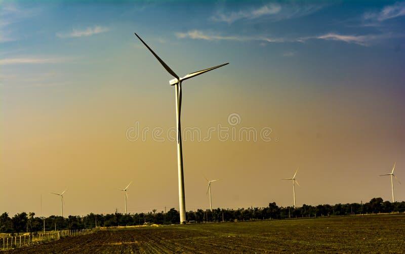 Vindturbiner på varm himmelbakgrund arkivfoto