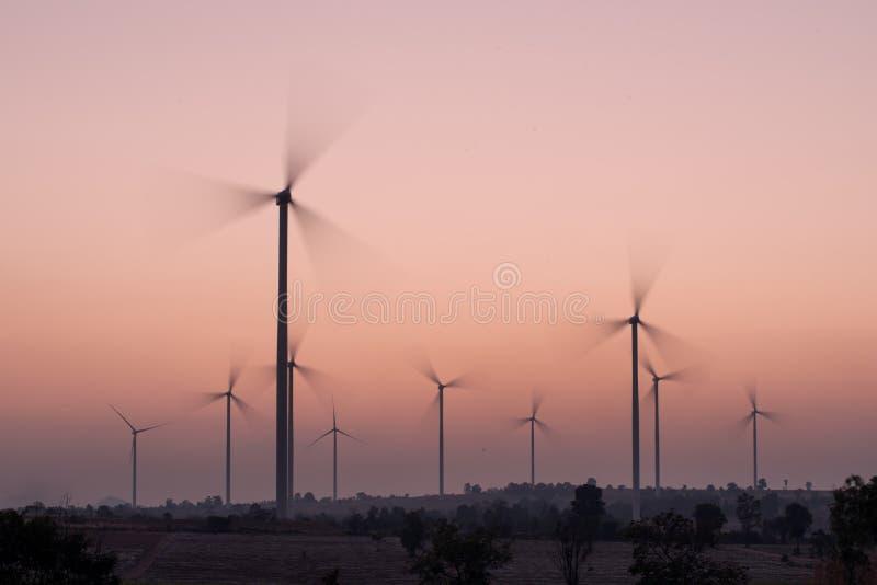 Vindturbiner som rotera på solnedgången arkivfoton