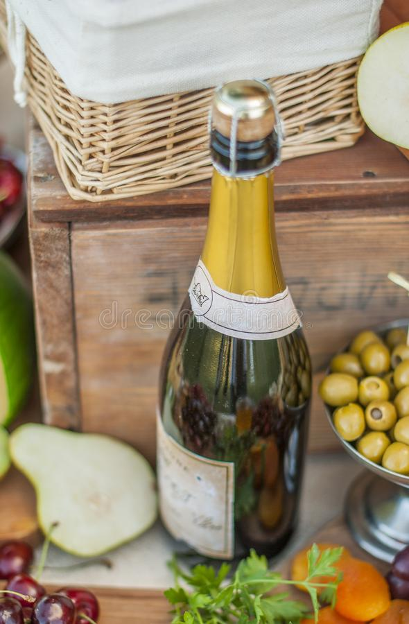 Vine bottle on a beautifully vintage decorated table. Vine bottle, Cheese and fruits on a beautifully vintage decorated table royalty free stock image