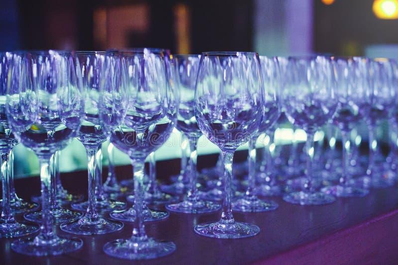 Vinexponeringsglas i sceniskt ljus, förberedelse för en bankett royaltyfri fotografi