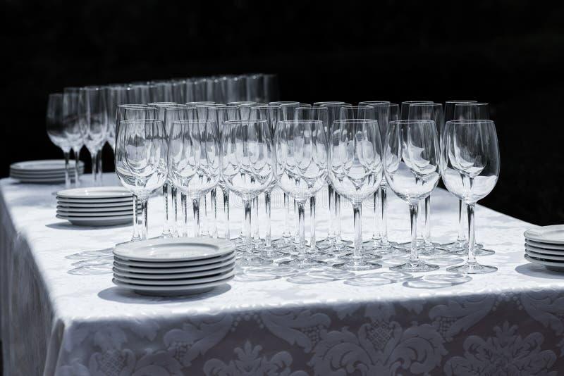 Vinexponeringsglas med plattor på tabellen royaltyfri bild