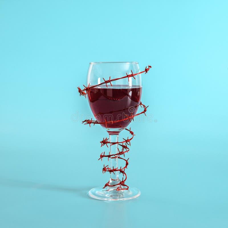 Vinexponeringsglas med r?tt vin som sl?s in med taggtr?d p? bl? bakgrund Begreppet av fara av alkoholism, b?jelse, v?gran av arkivbild