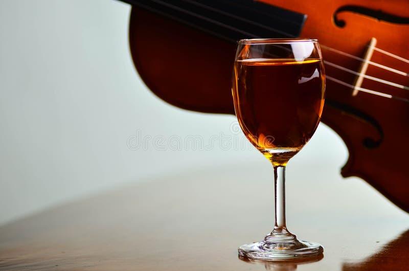 Vinexponeringsglas och fiol arkivbild