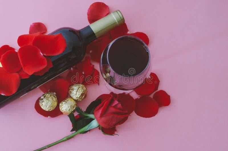 Vinexponeringsglas och röd ros med choklader, på rosa bakgrund valentin för dag s Top beskådar royaltyfri bild