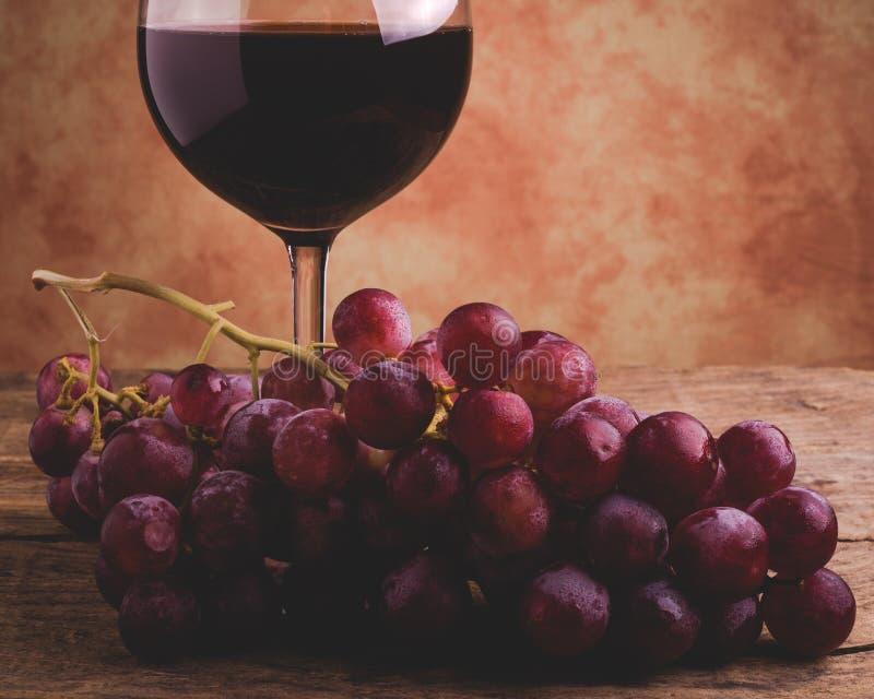 Vinexponeringsglas och röda druvor royaltyfri foto