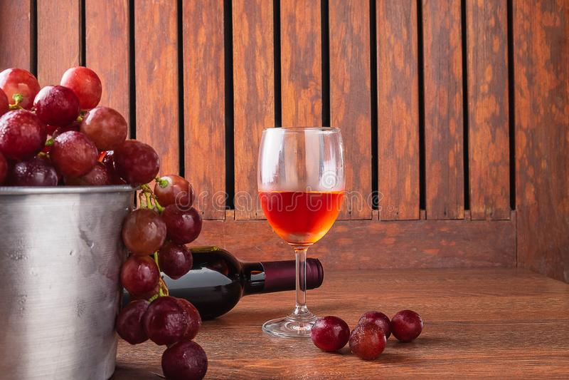 Vinexponeringsglas och vinflaska med röda druvor på träbakgrund arkivbilder