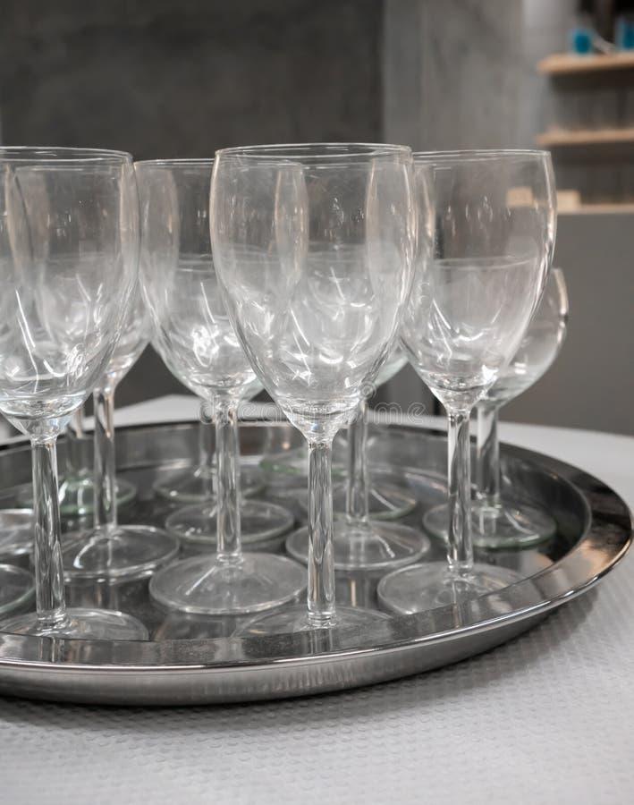 Vinexponeringsglas på silvermetallmagasinet på den vita tabellen royaltyfri fotografi