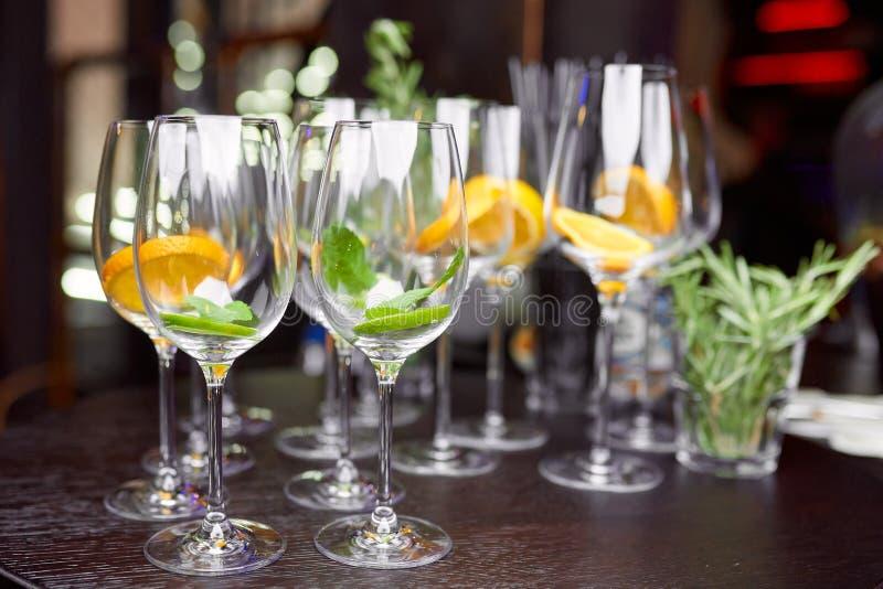 Vinexponeringsglas som fylls med citronen, limefrukt och mintkaramellen på en brun tabell royaltyfri foto