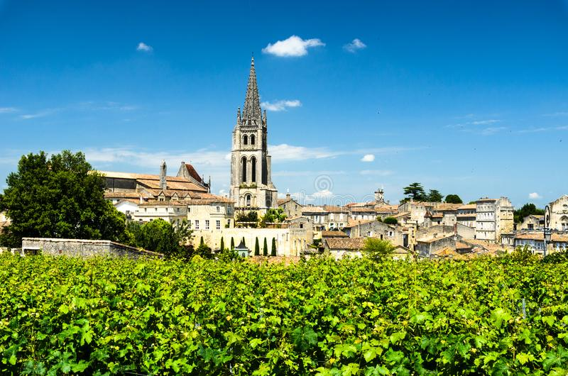 Bell tower of Saint-Emilion monolithic church through the vineyards. Vineyards with Church Bell tower on the background, Saint-Emilion, Bordeaux, France royalty free stock photo