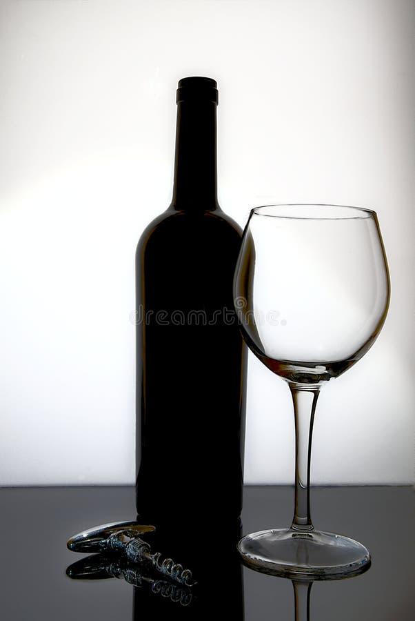 Vinflaska med ett exponeringsglas och en korkskruv royaltyfri bild