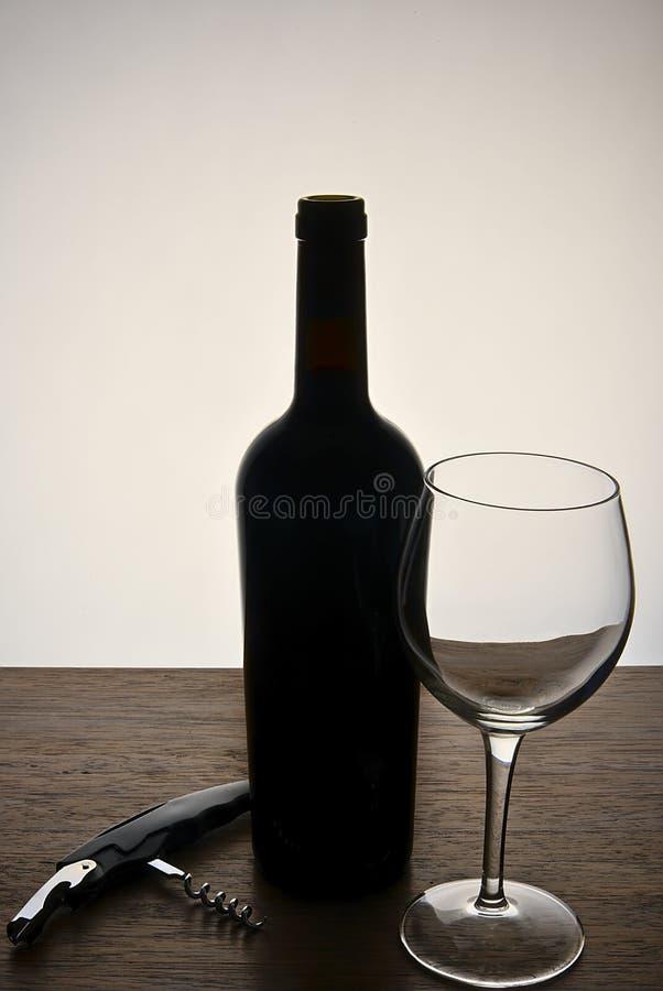 Vinflaska med ett exponeringsglas och en korkskruv royaltyfria foton
