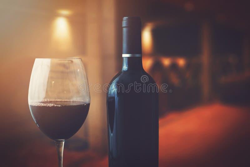 Vinflaska och exponeringsglas i vinkällare royaltyfria bilder