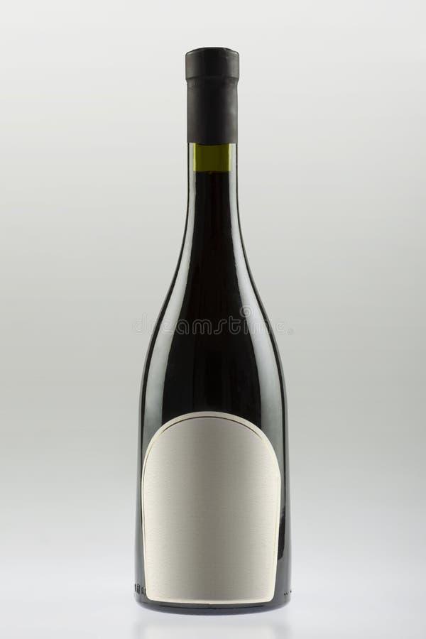 Vinflaskan med att slutta sidor och vitt botten, tömmer etiketten royaltyfria foton