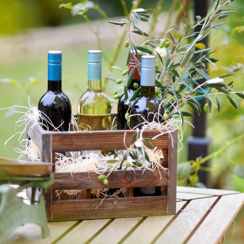 Vinflaskor i en träspjällåda arkivfoto