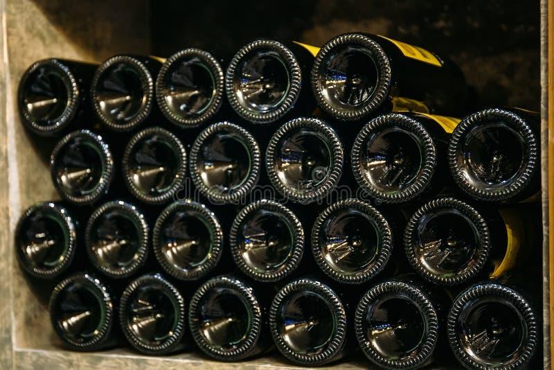 Vinflaskor på trähylla i marknads- eller vinlager arkivfoto