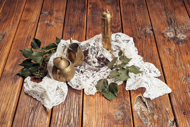 Ving een antieke die koffiemolen van messing, een kruik van de messingsmelk en een kom van de messingssuiker wordt gemaakt, op ee royalty-vrije stock foto