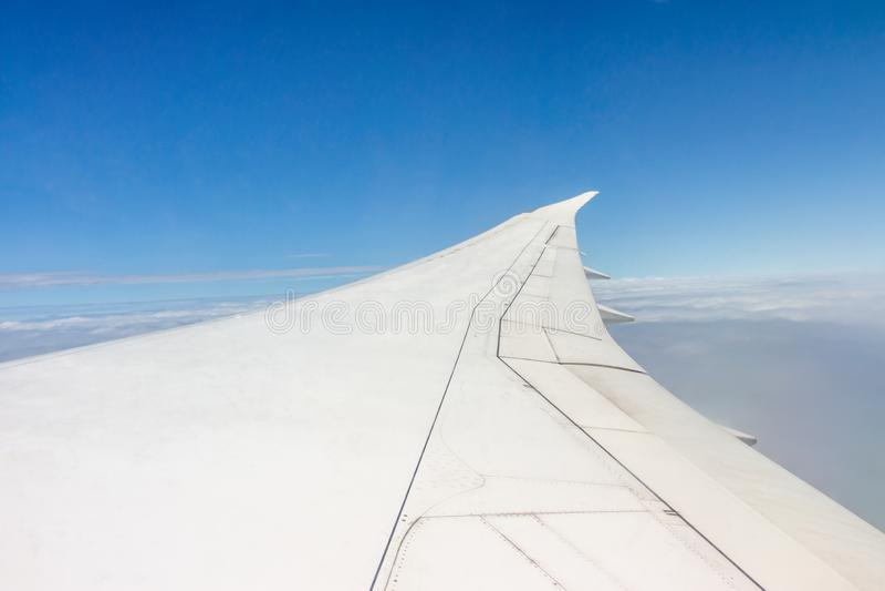 Vinge av ett flygplanflyg i himlen arkivbild
