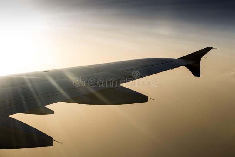 Vinge av ett flygplanflyg ovanför oklarheterna royaltyfri foto