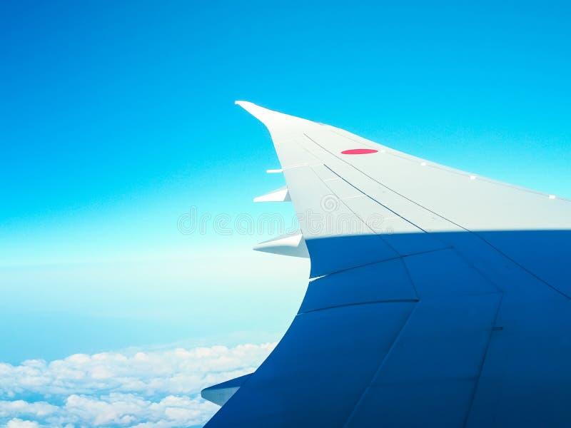 Vinge av flygplanet ovanför många vitmoln från blå himmel Japan för fönster fotografering för bildbyråer