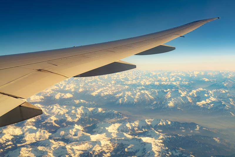 Vinge av nivån över bergräkningen med vit snö Flygplanflyg p? bl? himmel Scenisk sikt fr?n flygplanf?nster kommersiellt arkivfoton