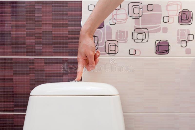 Vinger duwende knoop en spoelend toilet stock afbeelding