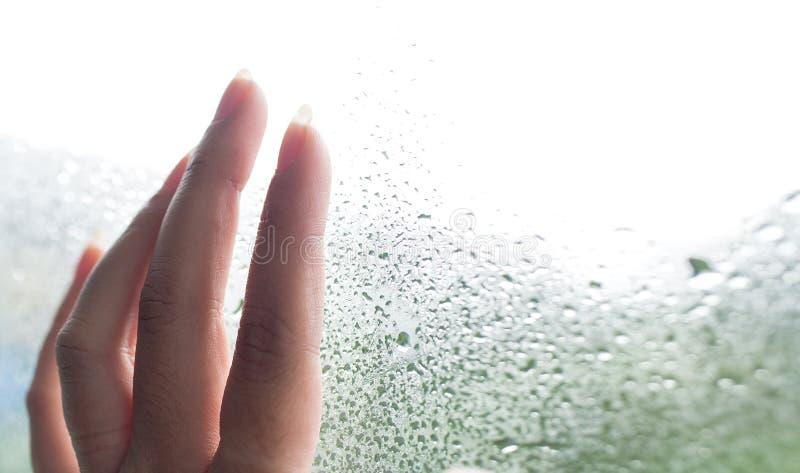 Vingers op het glas met waterdruppeltjes Hand jonge vrouw met vertroebeld op het venster Dalingen van Regen op Glasachtergrond se royalty-vrije stock foto